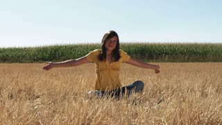 Girl in Sits in a Wheat Field in Front of Corn