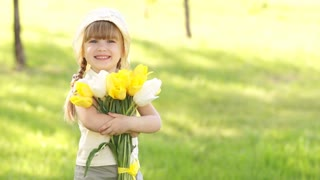 Girl is spinning with a bouquet of yellow tulips