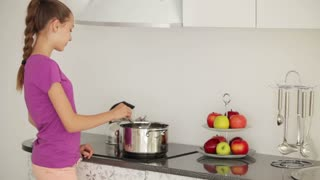 Girl is standing in the kitchen and stir the food in the pan