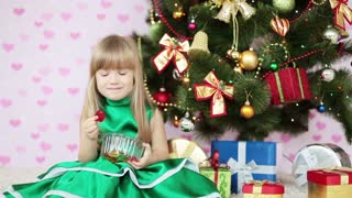 Girl is sweet. Child siting on the floor near a Christmas tree