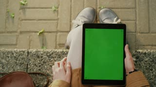 Girl is Using Tablet on Lap Outdoors at Sunny Day.