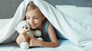 Girl kissing teddy bear. Child is under the blanket. Zooming