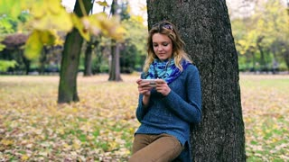 Girl leaning on tree and typing message on cellphone
