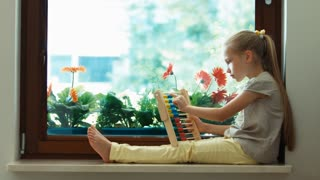 Girl learning to count with abacus and sitting on the sill. Zooming
