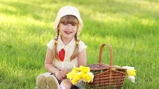 Girl licking a lollipop and sitting on the grass