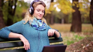 Girl listening music in headphones and using laptop in the park