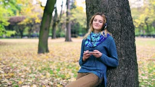 Girl listening music in the park and smiling to the camera