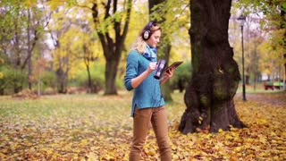 Girl listening music on headphones and drinking coffee in the park