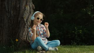 Girl listening to music. Girl is dancing while sitting under a tree and looking at camera. Zooming