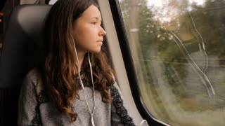 Girl listening to music with headphones, looking through the train window