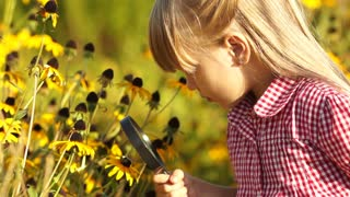 Girl looking at flower with a magnifying glass. Looking at camera