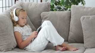 Girl lying on couch with tablet pc and listening to music