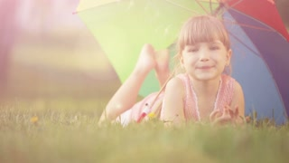 Girl lying on grass and smiling.  Lens flare and sunlight