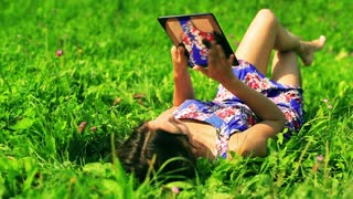 Girl lying on green meadow and surfing on tablet