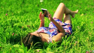 Girl lying on green meadow and talking on cellphone