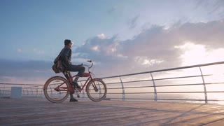 Girl on vintage bike enjoying beautiful sunrise on sea front