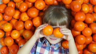 Girl orange. Happy child lying in oranges. Girl looking at camera