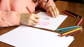 Girl painting heart on desk at home