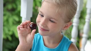 Girl putting a big cherry in her mouth and eating it