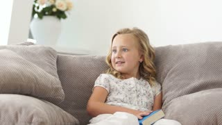Girl reading a book on sofa and  smiling