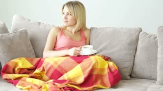 Girl resting on couch with cup of coffee. She covered with blanket