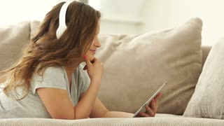 Girl resting on sofa and listening music