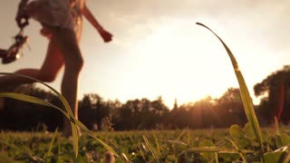 Girl running barefoot on the grass holding her high heels in hand. Super slow motion shot