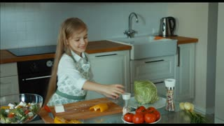 Girl salad sprinkles salt. Child chef in the kitchen. Zooming