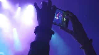 Girl shooting video with smartphone in the club at the concert, 4k