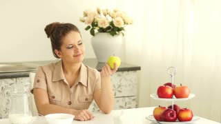 Girl sitting at table and holding an apple