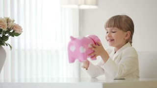 Girl sitting at table and holding piggy bank