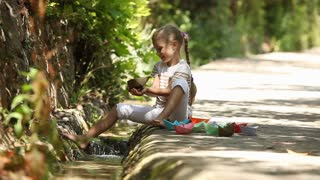 Girl sitting beside a stream and launching a lot of paper boats on water