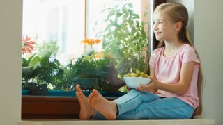 Girl sitting on a windowsill and eating gooseberries and looking at camera. Thumb up. Ok. Zooming