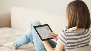 Girl sitting on sofa with tablet pc and looking at camera