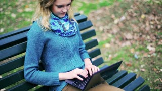 Girl sitting on the bench in the park and working on laptop