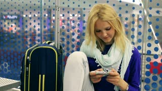 Girl sitting on the station and texting on smartphone