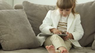 Girl sitting with tablet and smiling