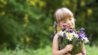 Girl smelling flower in the open space