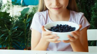 Girl sniffing and showing bowl with blueberries at camera. Closeup