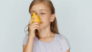 Girl sniffing lemon and laughing at camera. Thumb up. Ok. Closeup