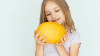 Girl sniffing melon and showing berry and laughing at camera. Closeup