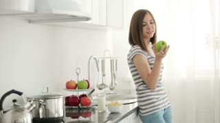 Girl standing in kitchen and bitting juicy apple