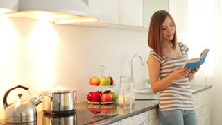 Girl standing in kitchen and finishes reading book.After she pours milk into glass and drinks it