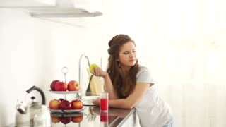 Girl standing in kitchen and holding an apple