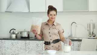 Girl standing in kitchen with corn flakes and milk