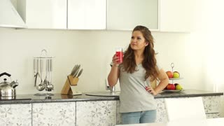 Girl standing in the kitchen with a glass of juice