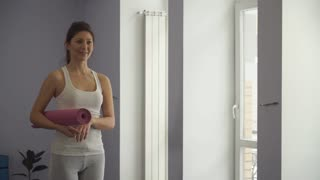 Girl standing with yoga mat getting ready to exercise.