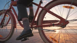 Girl starting to ride vintage bike on seafront at sunrise, close up shot
