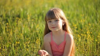 Girl straightens her hair and sitting in a field