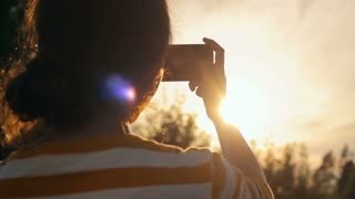 Girl taking a photo of sunset with a smartphone in nature, close-up, camera movement